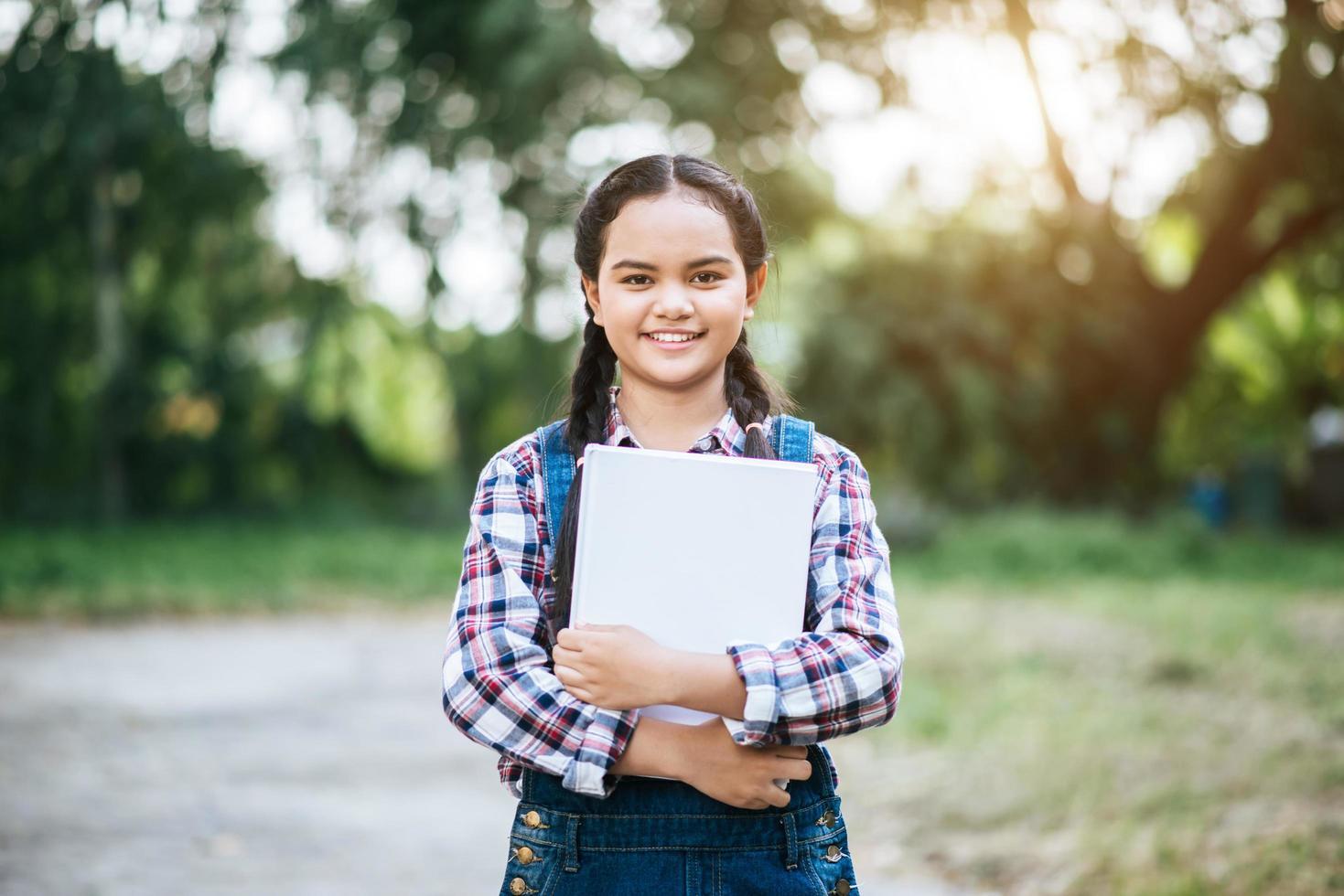 giovane studentessa in possesso di un libro foto