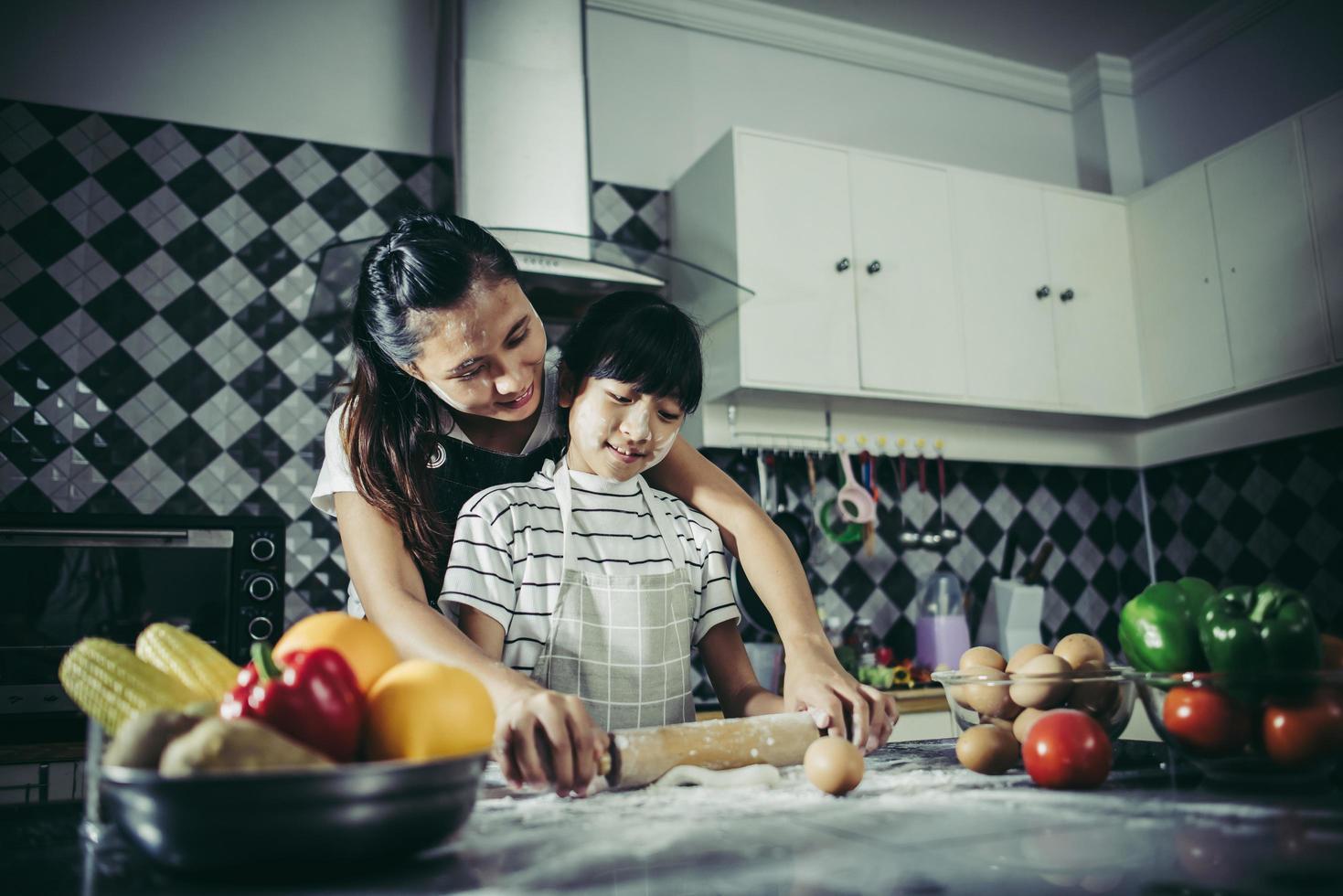 bambina carina e mamma in grembiuli che appiattiscono la pasta nella cucina di casa foto