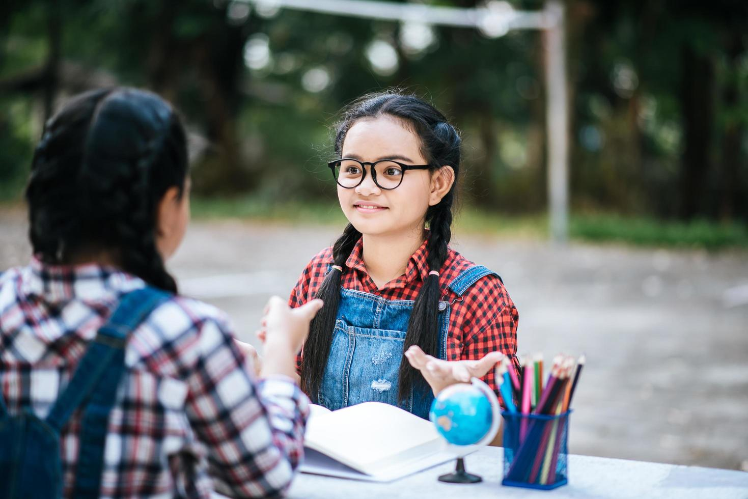 due ragazze che studiano e parlano tra loro in un parco foto
