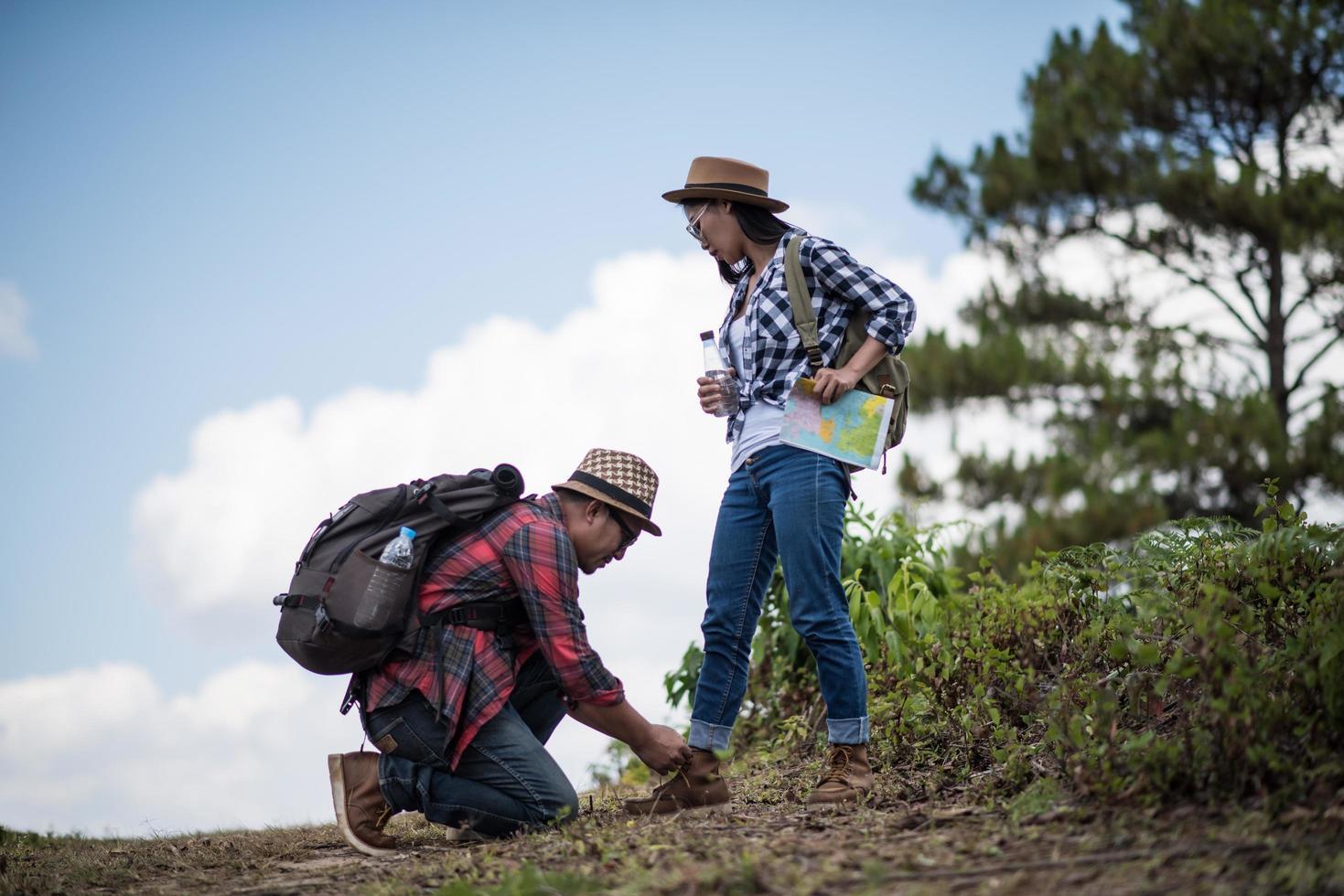 giovane che lega le scarpe per escursionista femminile foto