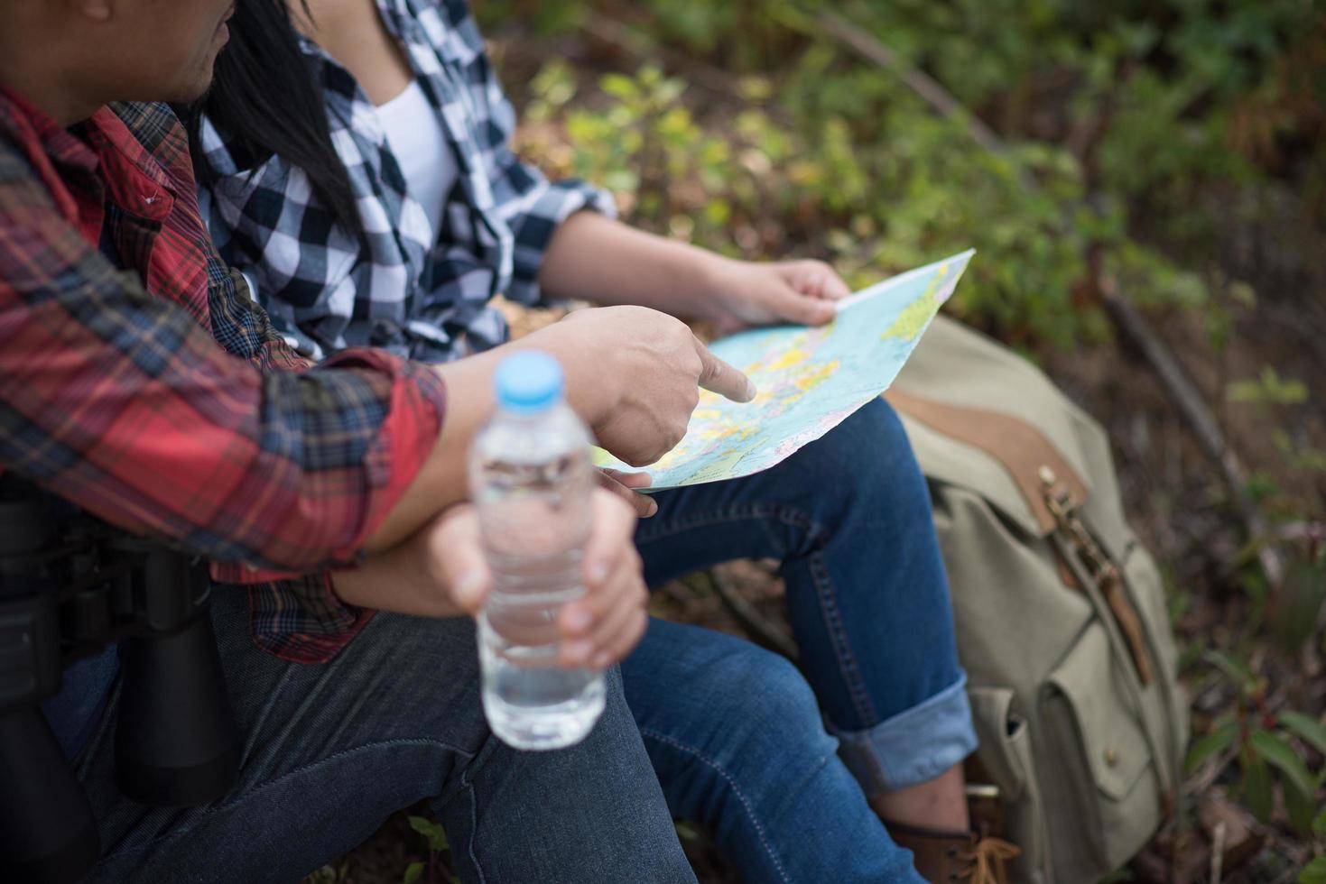 giovane coppia guardando la mappa durante le escursioni nella foresta foto