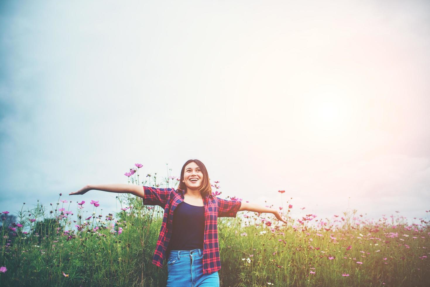 felice giovane donna alzando le mani in un prato foto