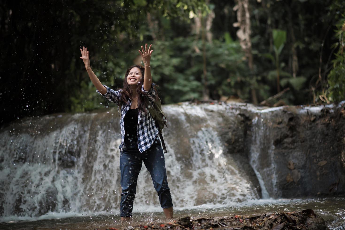 giovane donna che ha divertimento sotto una cascata nella foresta foto