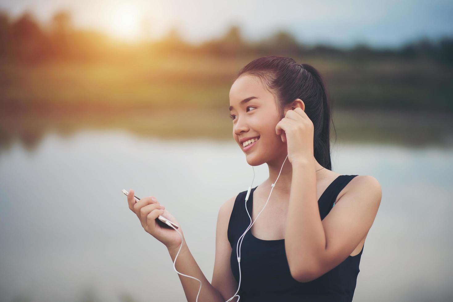 adolescente fitness con auricolari ascoltando musica durante il suo allenamento foto