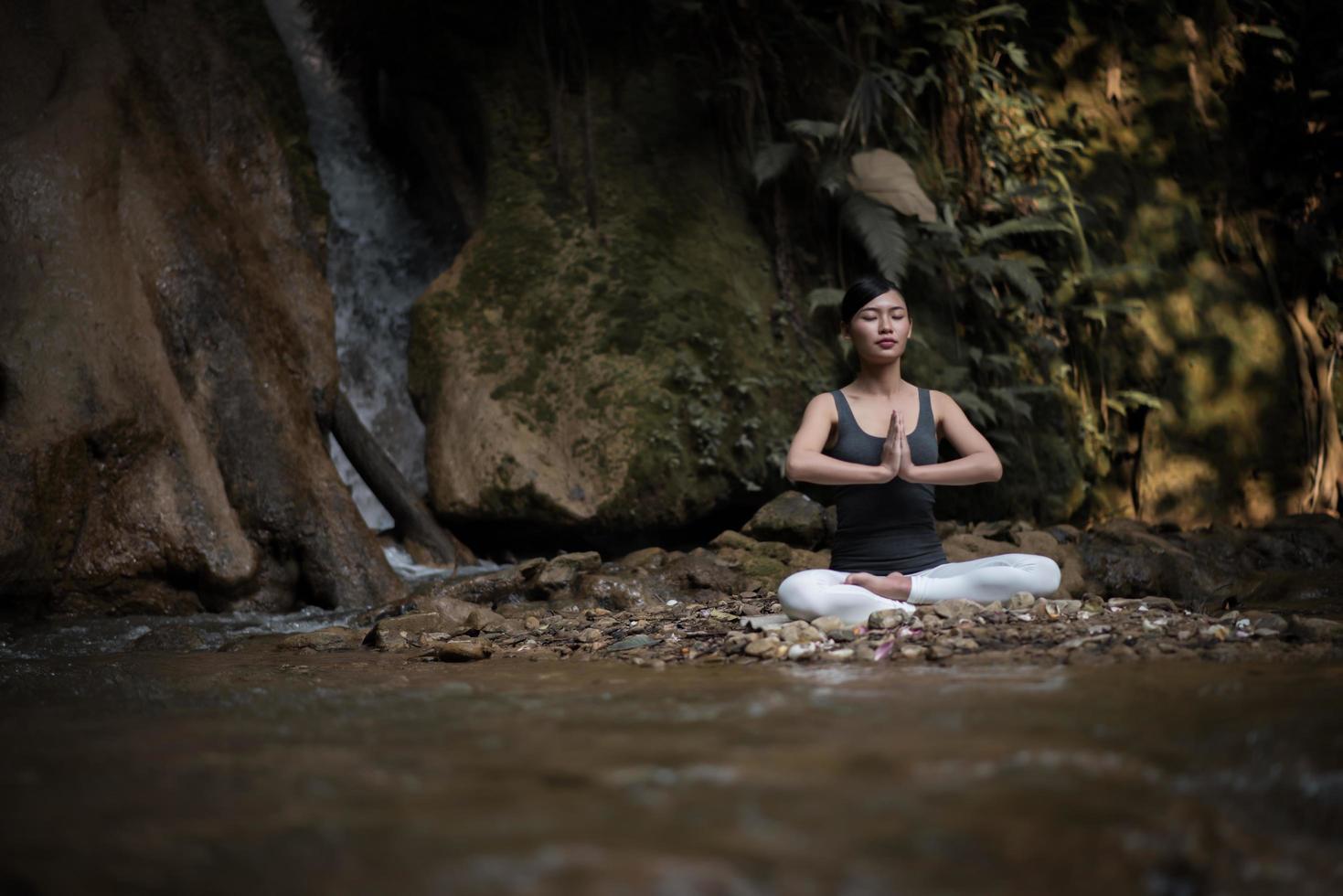 giovane donna in una posa yoga seduto vicino a una cascata foto