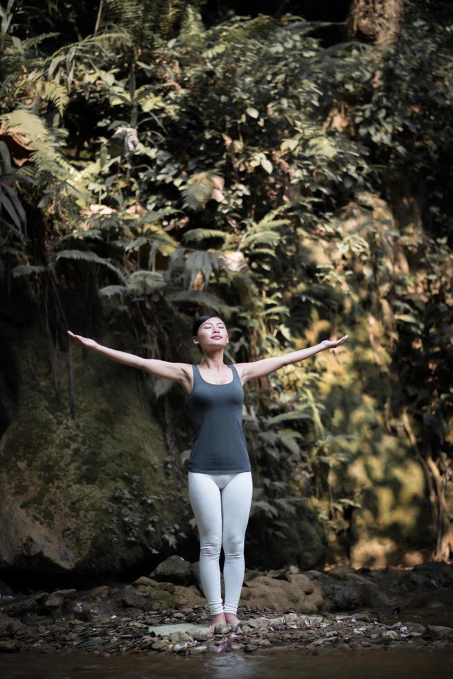 giovane donna in una posa yoga vicino a una cascata foto