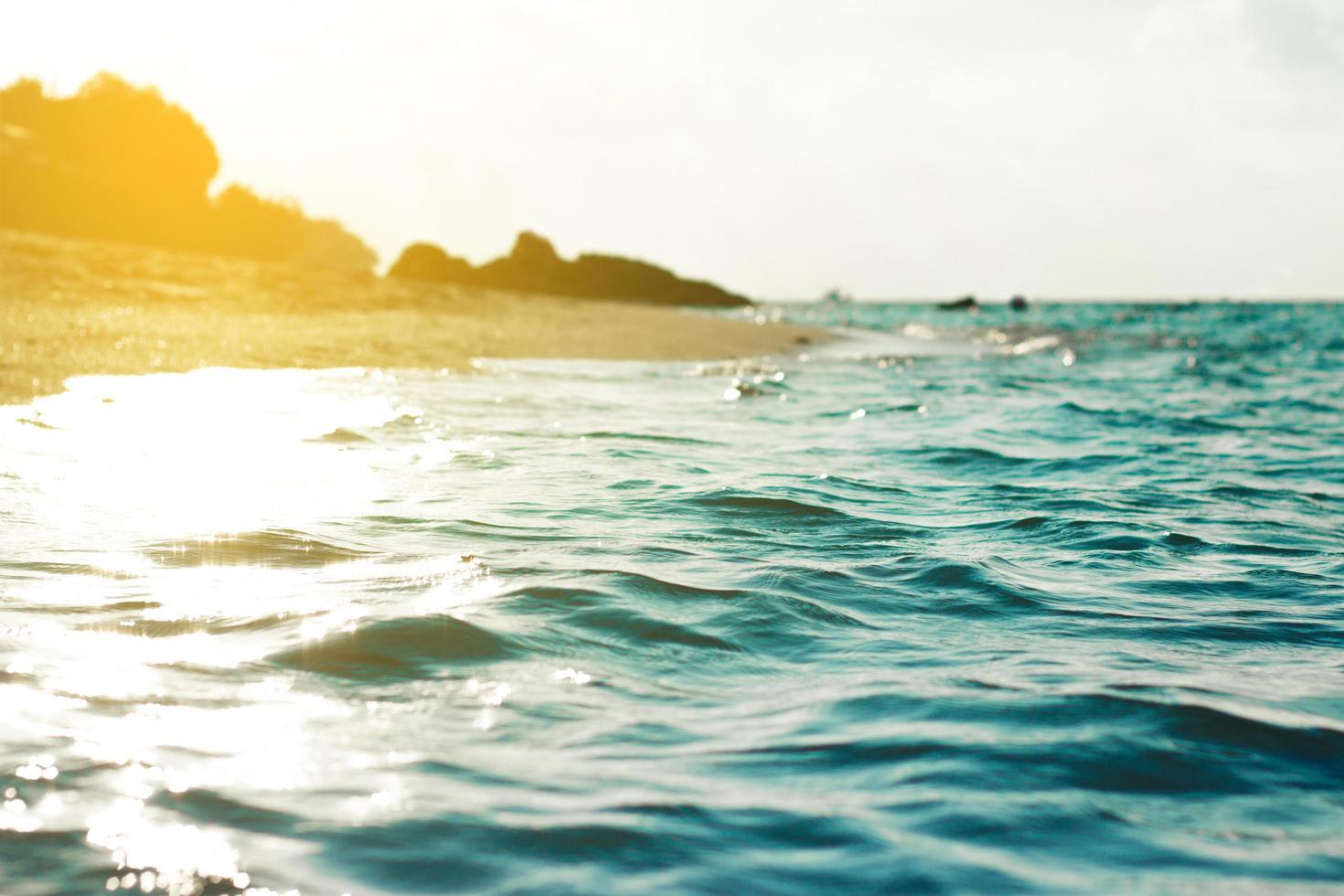sabbia e acqua in spiaggia con cielo blu chiaro foto