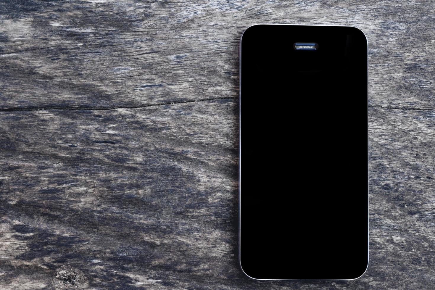 vista superiore dello smartphone mobile dello schermo nero di mockup sul vecchio fondo di legno in bianco della tavola. vista dall'alto telefono piatto laici e copia spazio per il concetto di business. foto