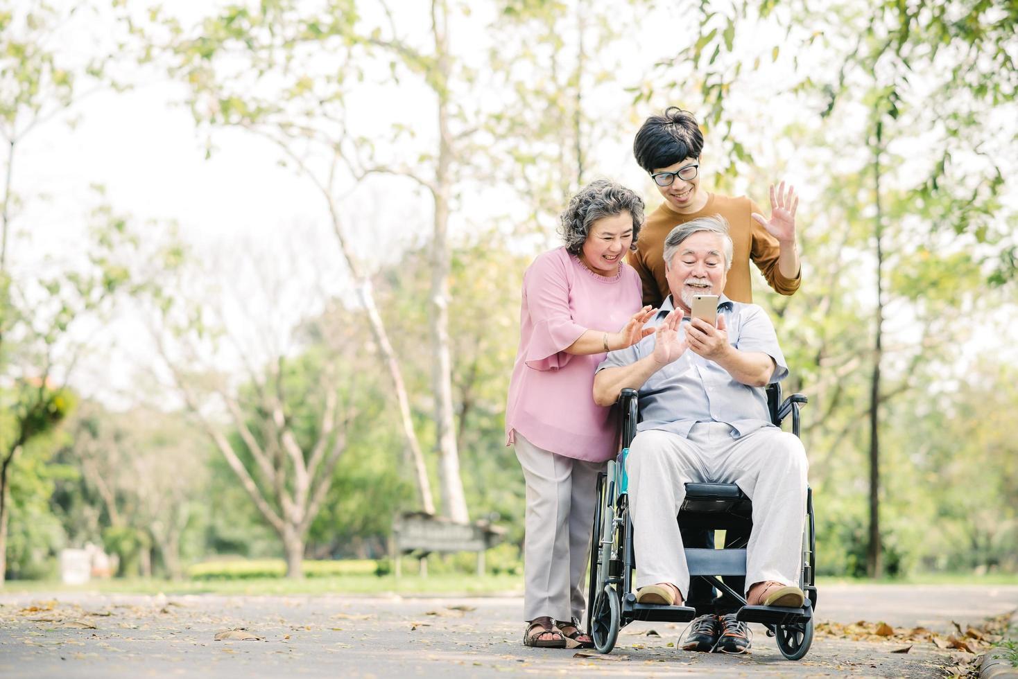 famiglia divertendosi utilizzando smartphone nel parco foto
