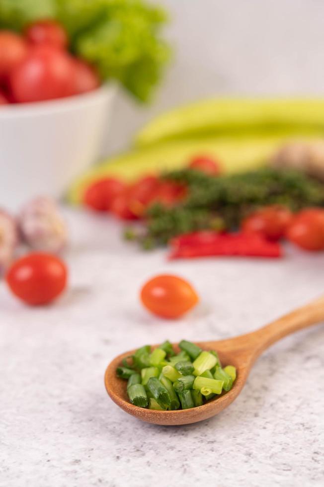 cipollotto tritato in un cucchiaio di legno con peperoni e pomodori foto