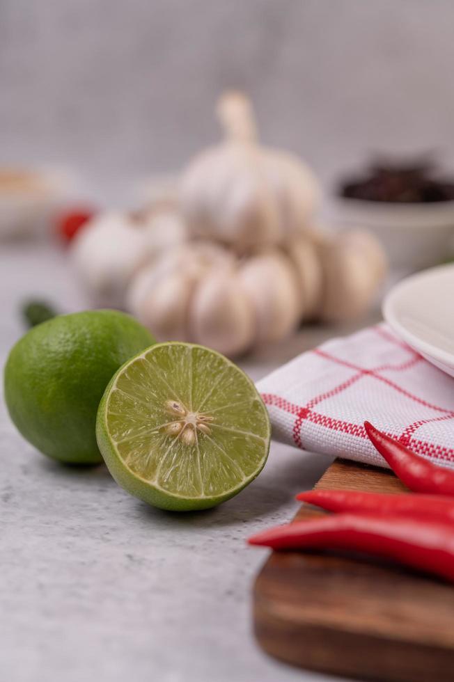 limone tagliato a metà con peperoncino e aglio su uno sfondo bianco foto