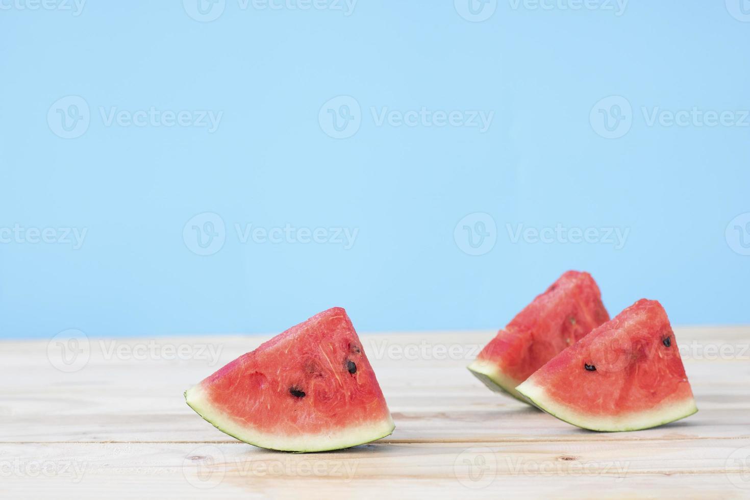 tre pezzi di anguria su un tavolo di legno foto