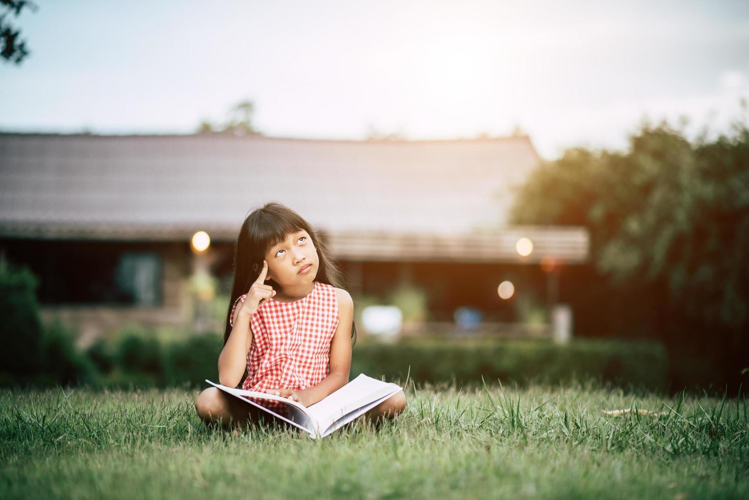 bambina che legge un libro nel giardino di casa sua fuori foto