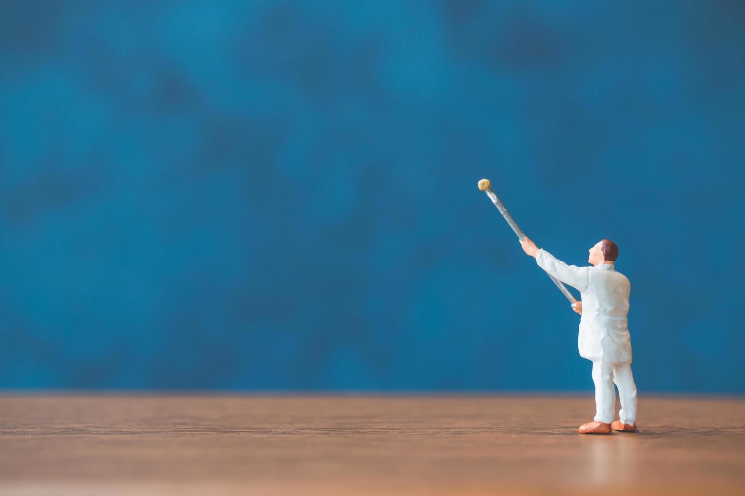 persona in miniatura in possesso di un pennello davanti a sfondo blu muro foto