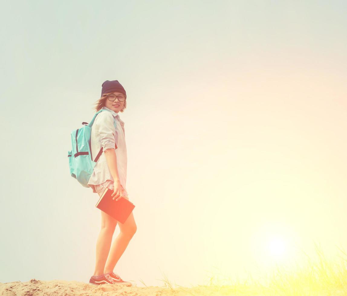 bella giovane donna che legge un libro in spiaggia foto