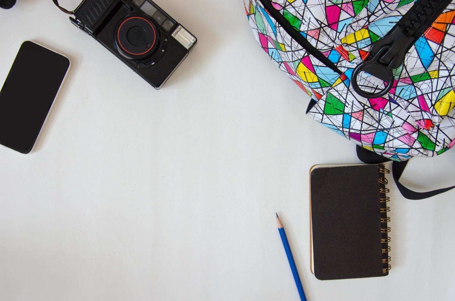 backback, notebook e fotocamera su un tavolo foto