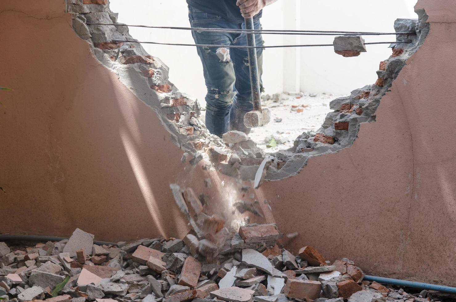 uomo che demolisce le pareti di una casa foto