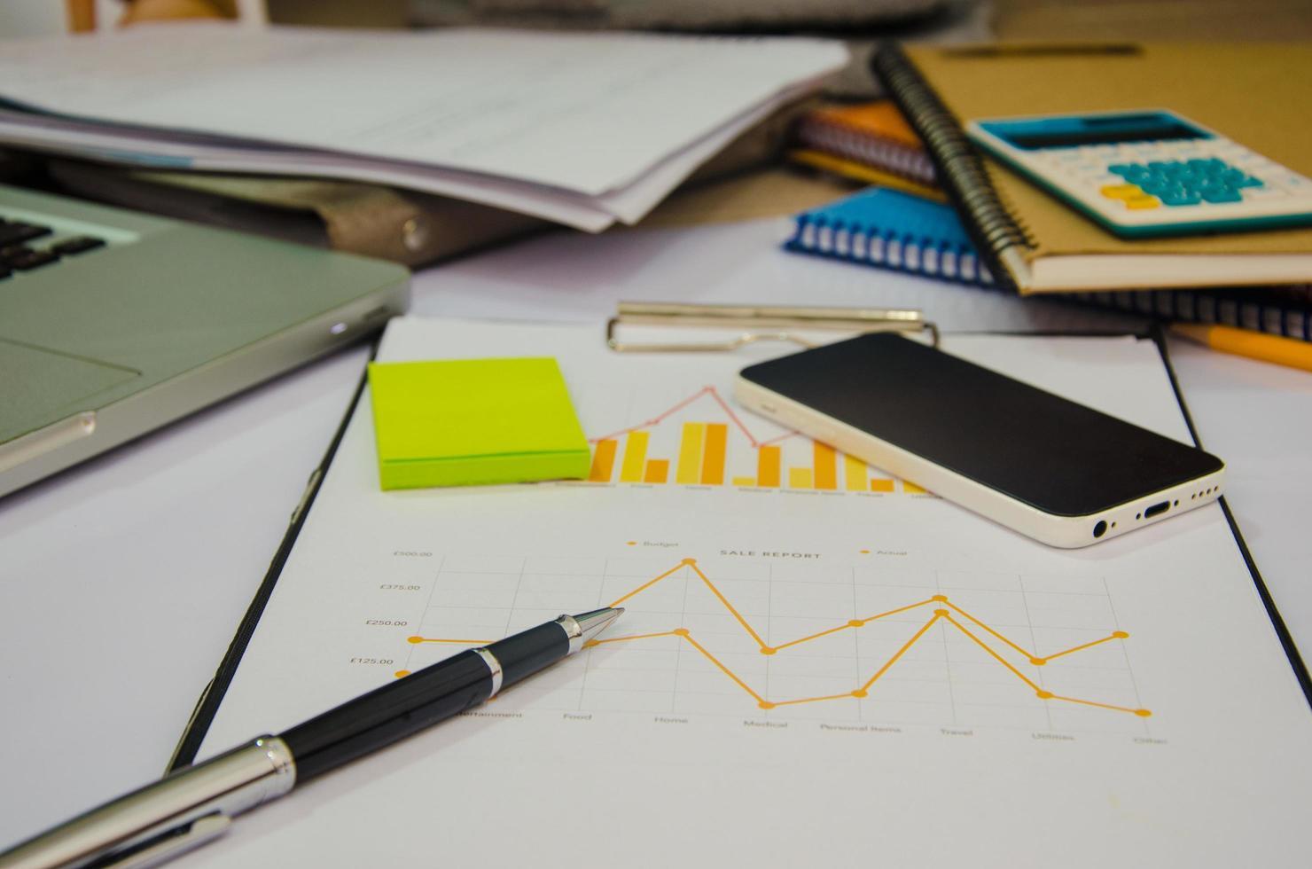scrivania disordinata con grafico su una lavagna per appunti foto