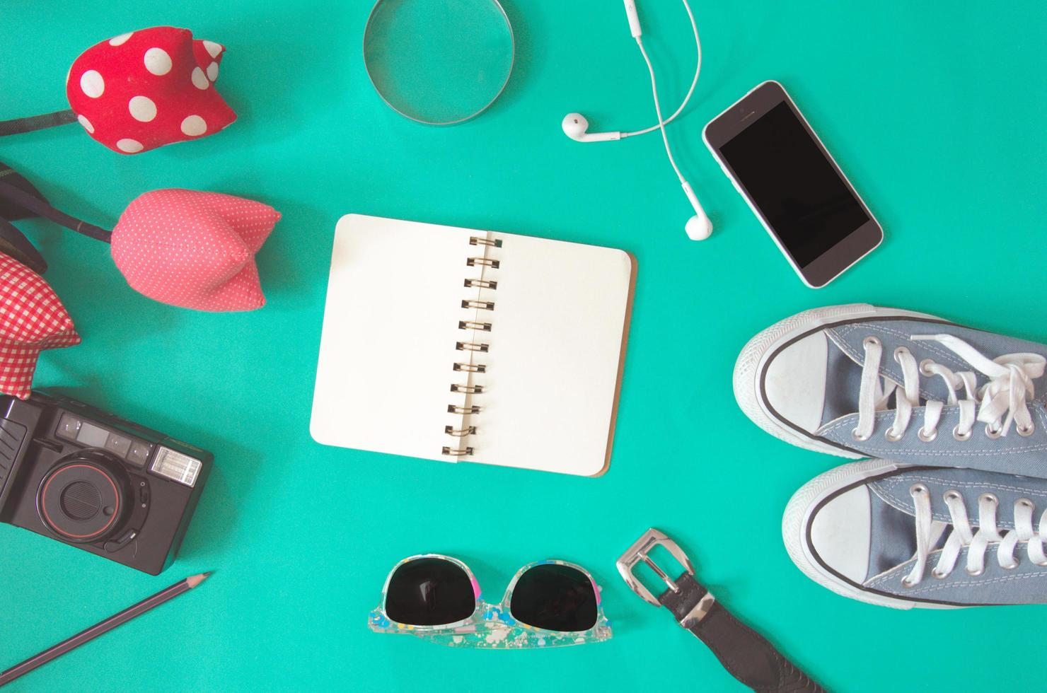 disposizione piatta di notebook, occhiali da sole, fotocamera e converse foto