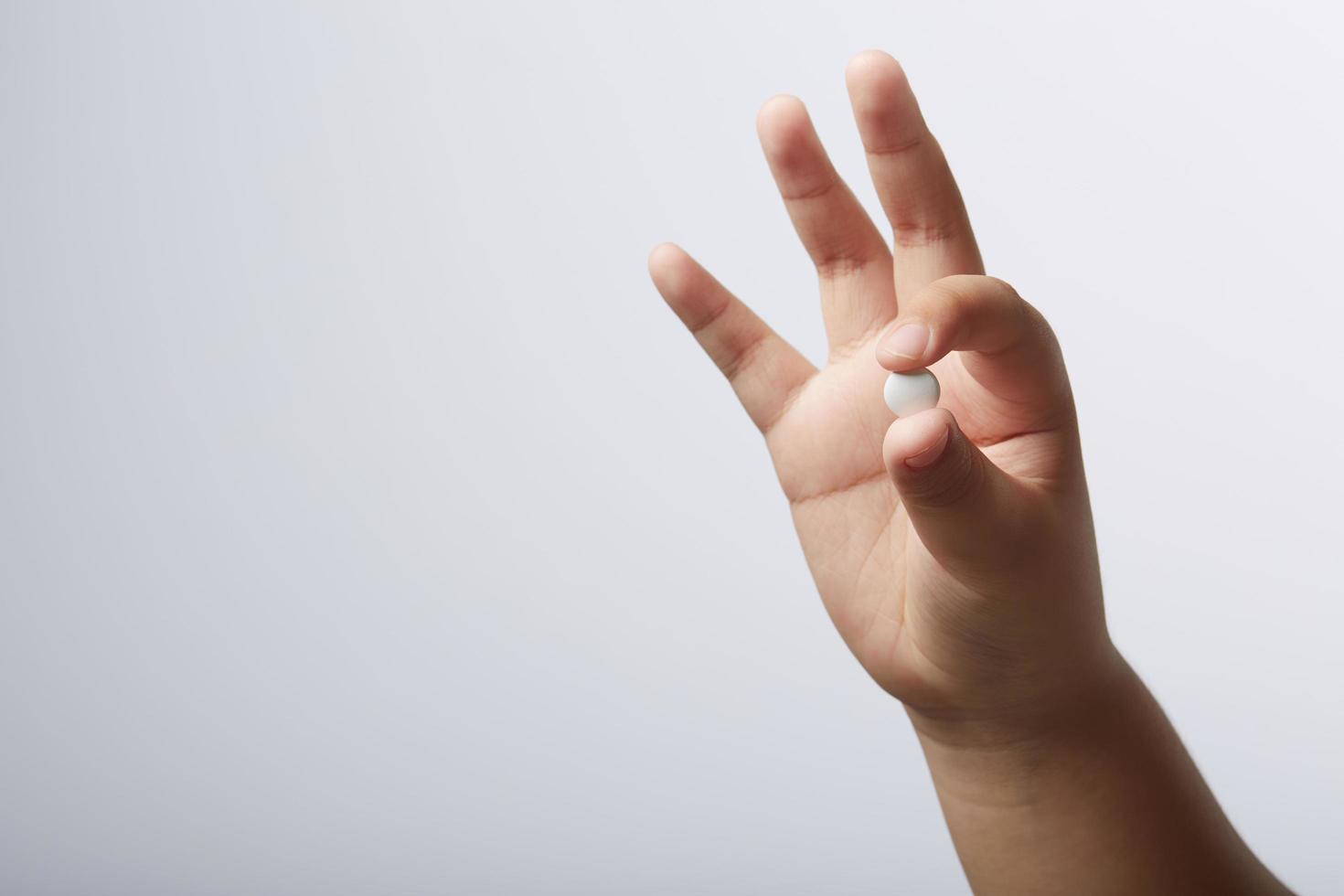 mano che tiene la pillola foto