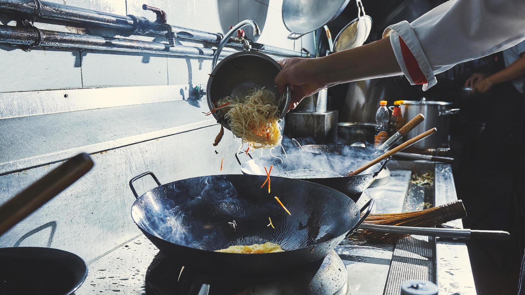 chef che cucina il cibo nel wok foto