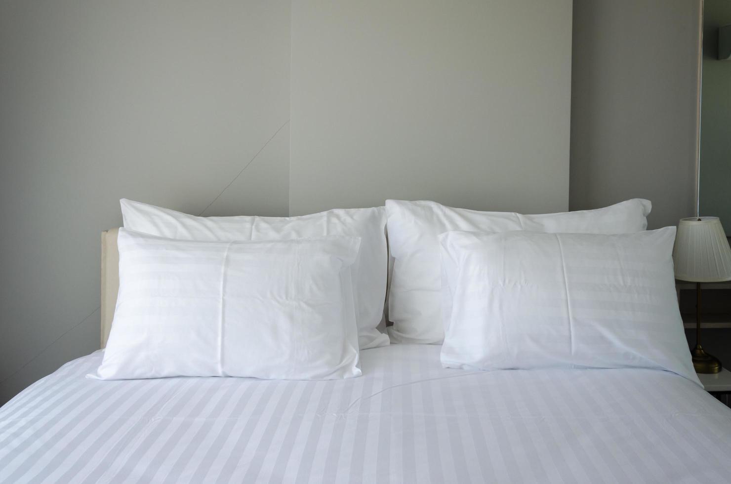 cuscini bianchi sul letto dell'hotel foto