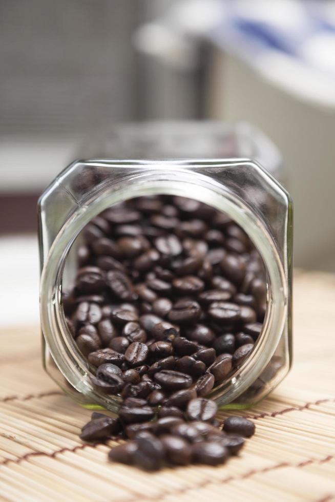 chicchi di caffè fuoriusciti dalla bottiglia foto