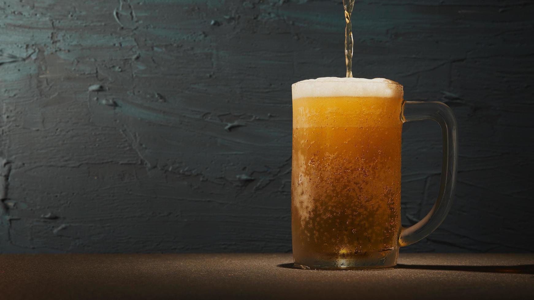 birra che viene versata in una tazza foto
