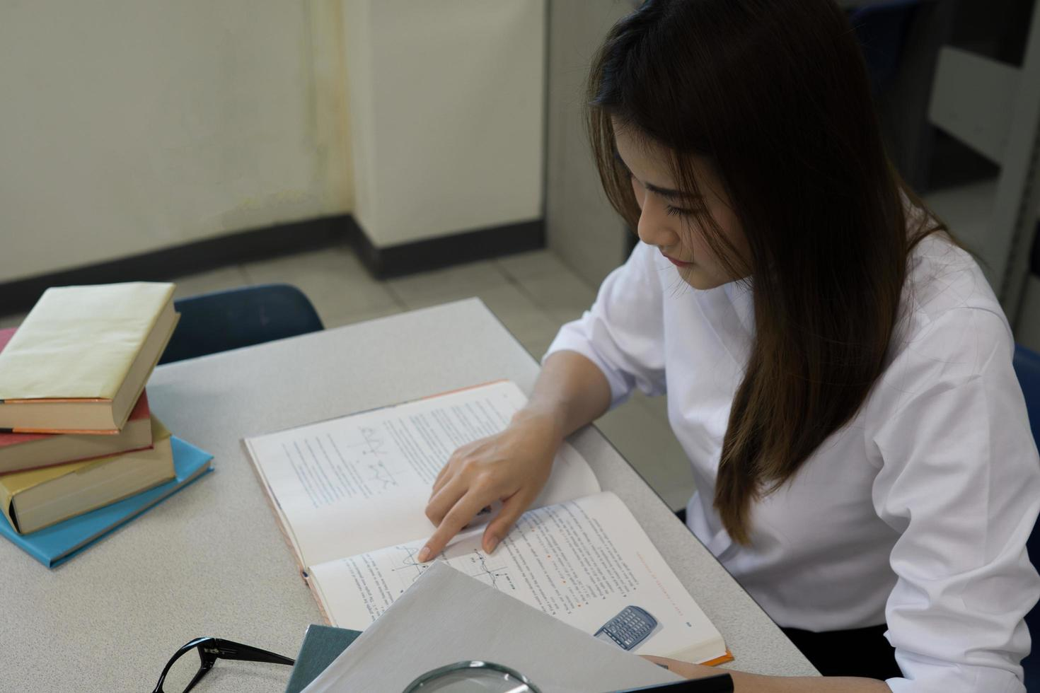 giovane studente asiatico che legge in biblioteca foto