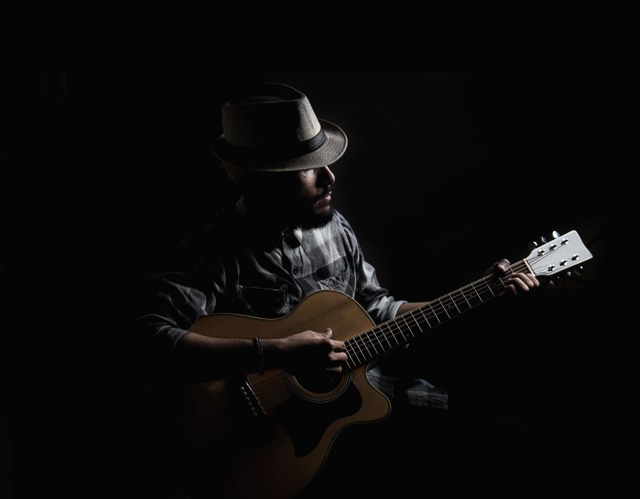 chitarrista giovane hipster su sfondo scuro foto