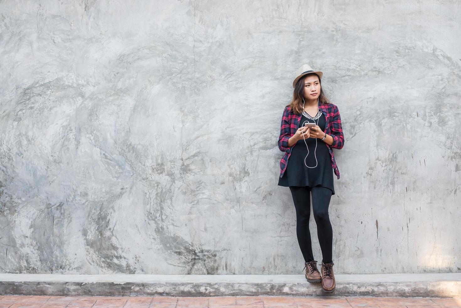 ritratto di una donna giovane hipster che ascolta la musica con lo smartphone foto