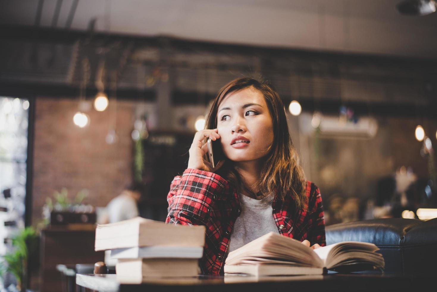 adolescente hipster seduto e godendo di un libro in un caffè foto