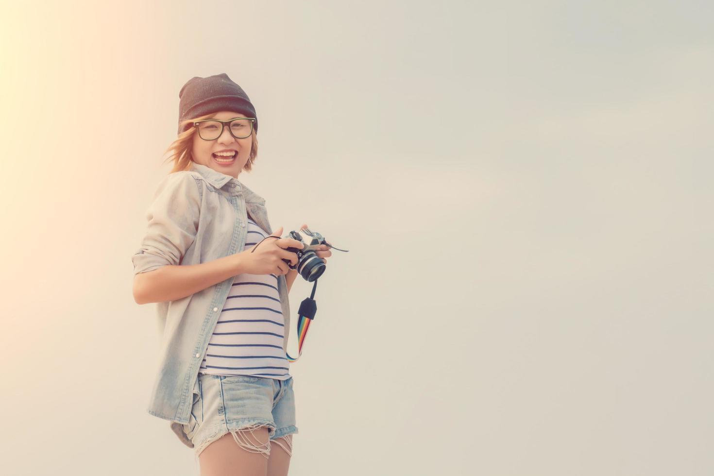 bella giovane donna fotografo tenendo la fotocamera retrò foto