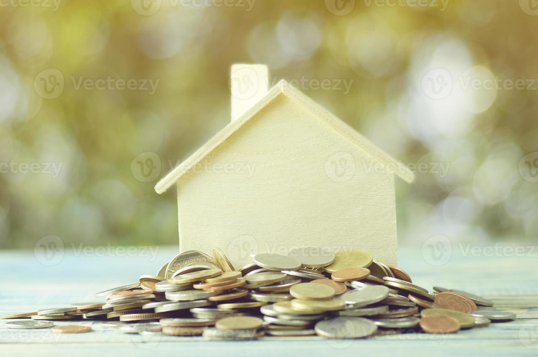 mucchio di monete con una piccola casa modello foto