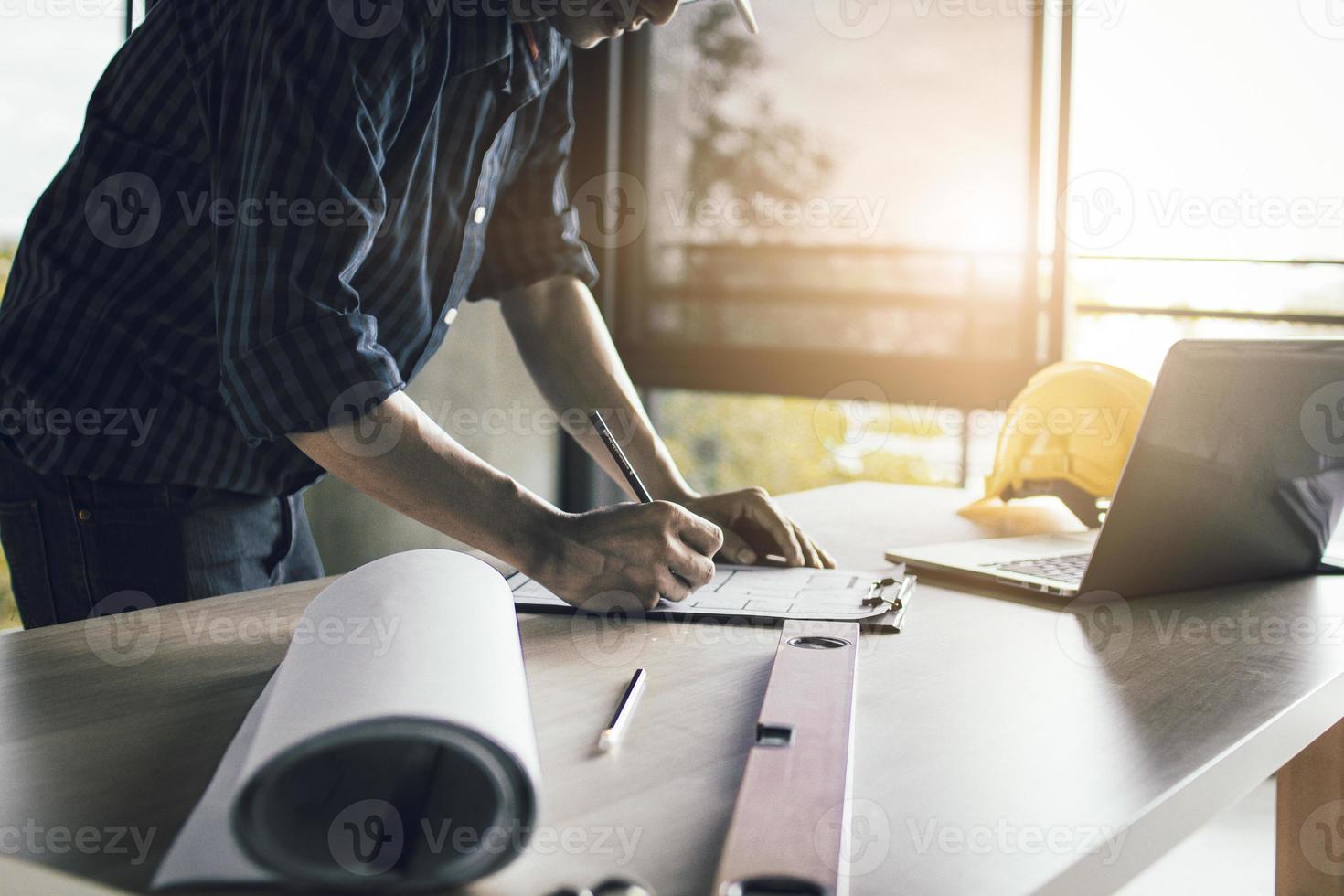uomo che lavora su progetti a una scrivania in piedi foto