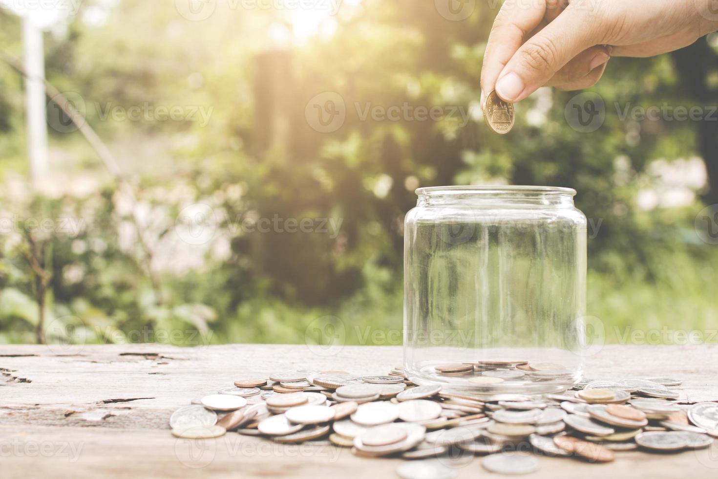 mano mettendo soldi moneta in un barattolo di vetro foto
