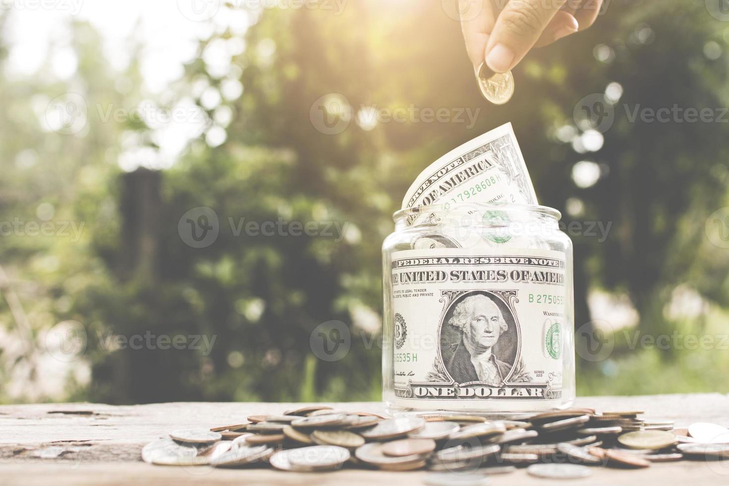 risparmiare denaro concetto, mettere mano soldi in un barattolo di vetro foto