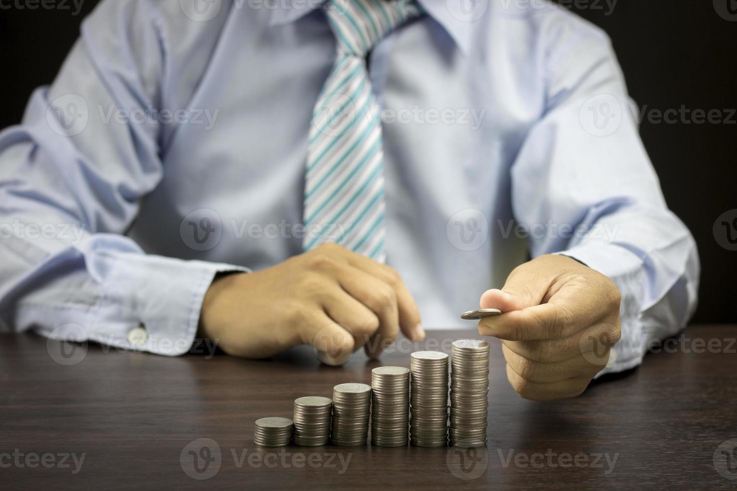 uomo d'affari impilando monete foto