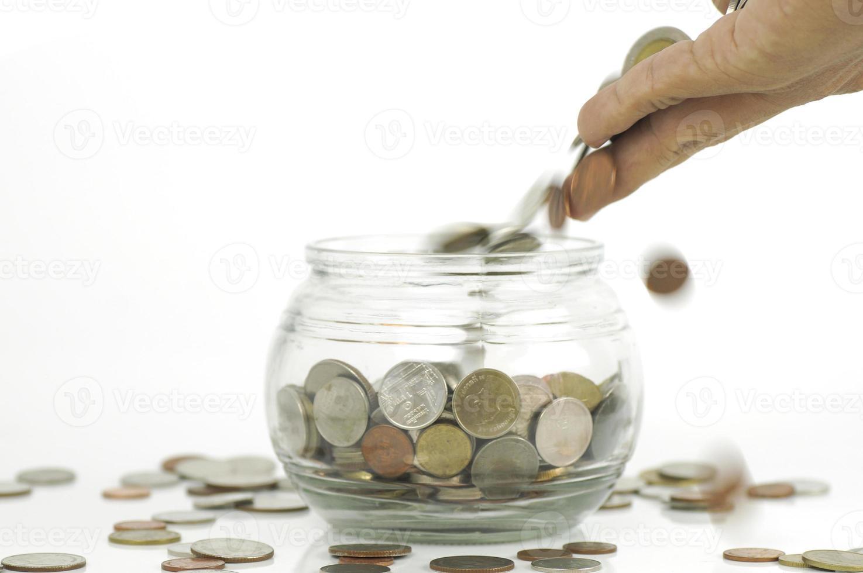 mano che mette soldi in un barattolo foto