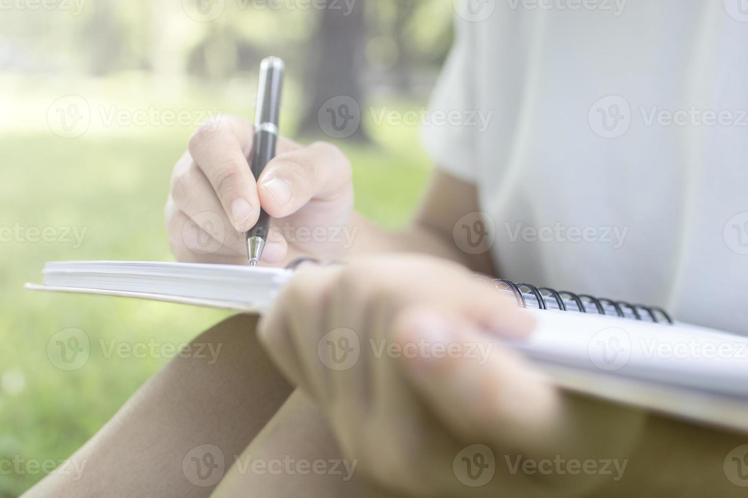 persona seduta e scrivendo nel parco foto