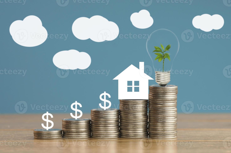 mucchio di monete e modello di casa con piccolo albero verde e lampadina foto