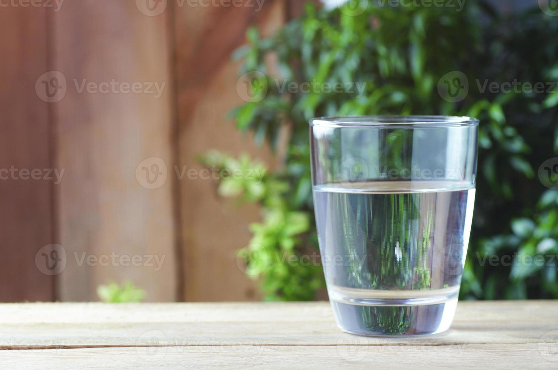 bicchiere di acqua potabile su uno sfondo di legno foto