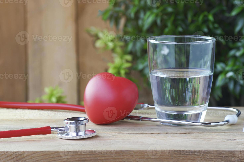 stetoscopio e cuore rosso con acqua su uno sfondo di legno foto
