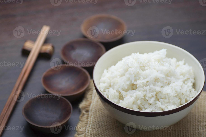 riso bianco tailandese con le bacchette su fondo di legno foto