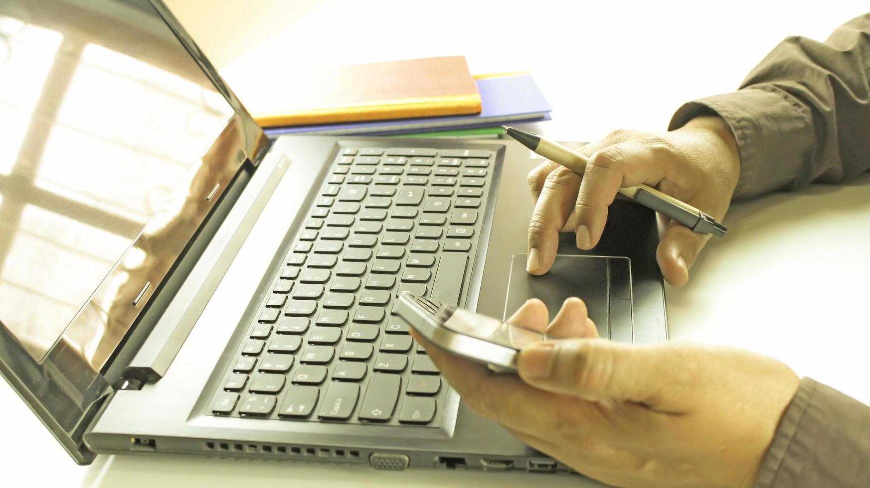 professionista che lavora su laptop e telefono foto