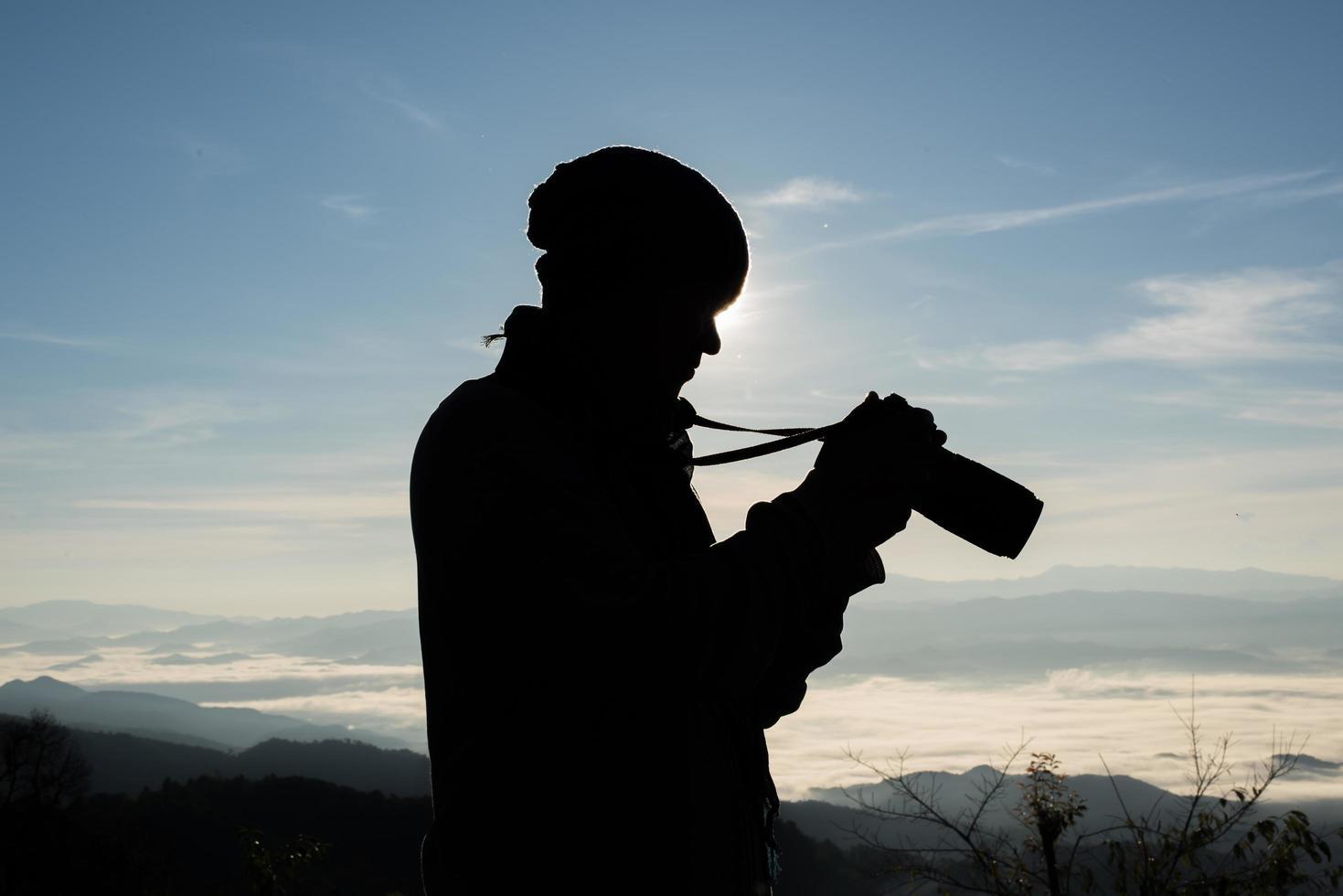 silhouette di giovane fotografo che tiene una macchina fotografica con paesaggio di montagna foto