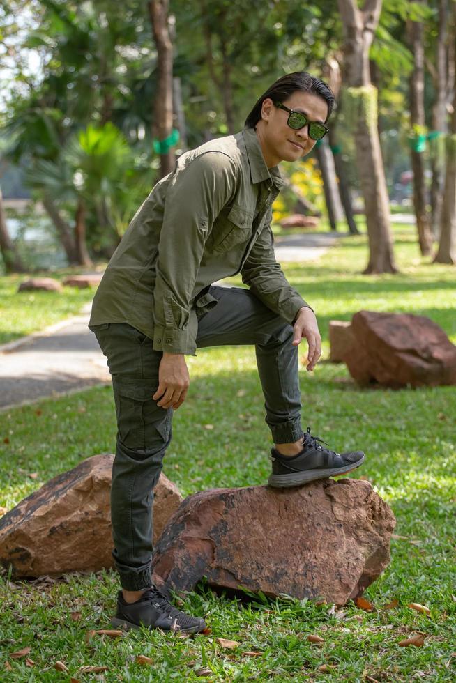 ritratto di felice giovane asiatico in camicia a maniche lunghe e pantaloni verdi in piedi nel parco foto