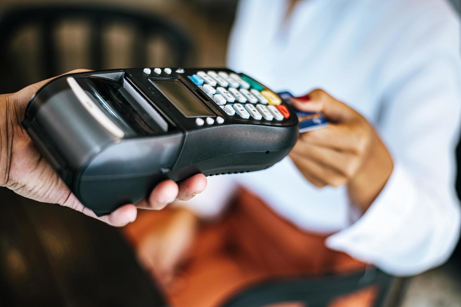 primo piano della donna che paga con carta di credito nella caffetteria foto