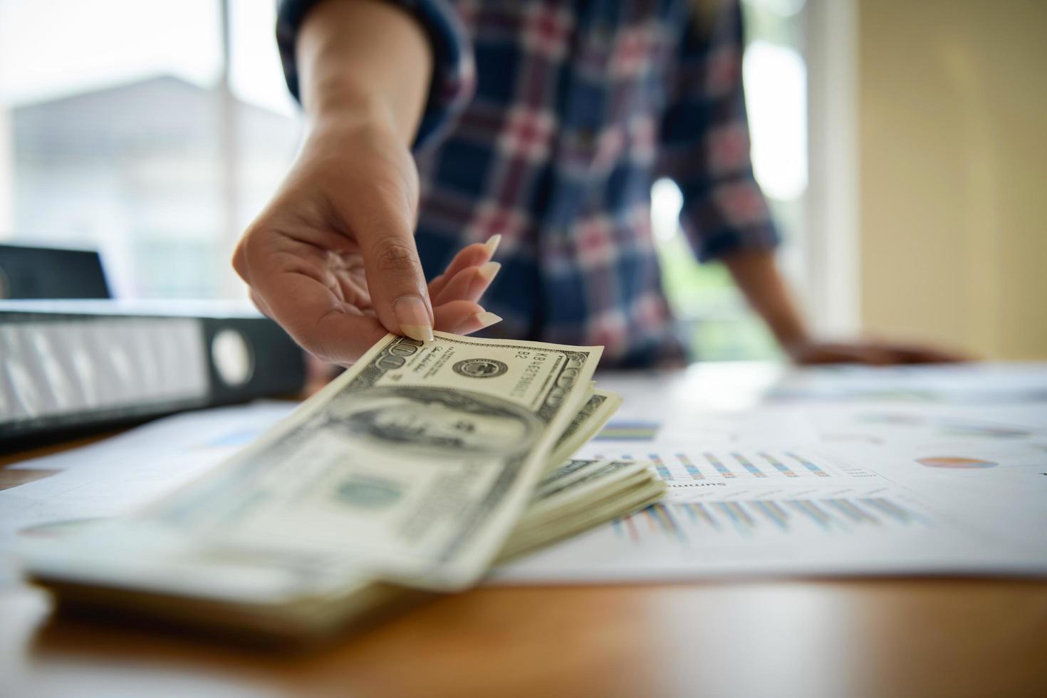 giovane donna d'affari controlla banconote in dollari foto