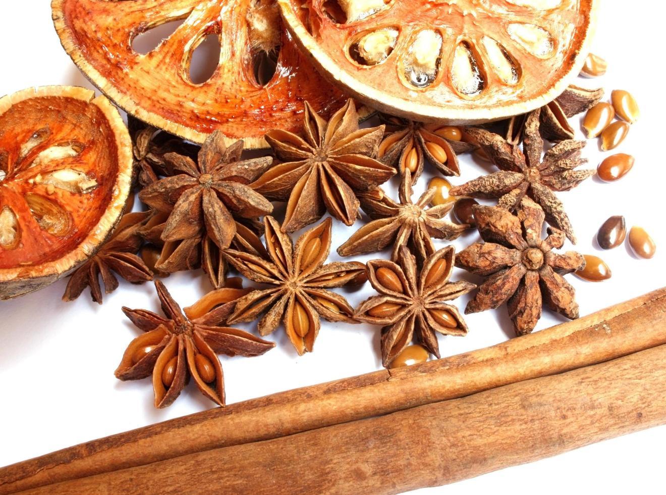 bastoncini di cannella, anice stellato e mele cotogne essiccate su bianco foto